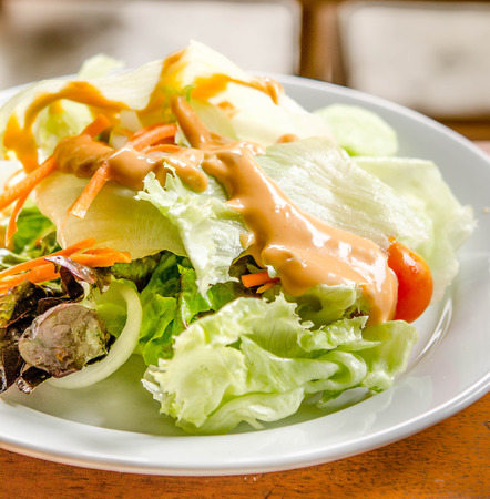 topped: Fresh vegetable salad  with thousand island dressing Stock Photo
