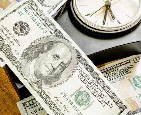 Stack of one hundred dollar bills with clock. Dof view photo