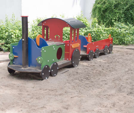children play area: Big colorful toy train in the sand