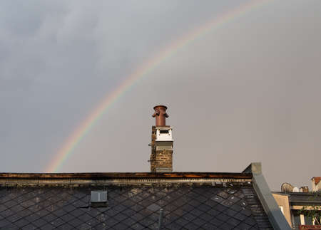 housetop: Rainbow behind a chimney Stock Photo