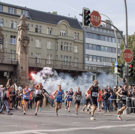 spectator: BERLIN, GERMANY - SEPTEMBER 25, 2016: Spectator With A Torch And Runners At Berlin Marathon 2016 Editorial