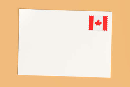 canada stamp: Letter Or Postcard From Canada: Blank White Card with Canadian Flag Postage Stamp, 3d Illustration On Wooden Color