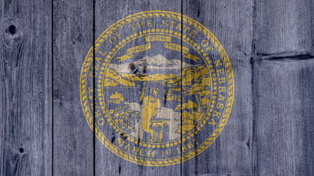 USA Politics News Concept: US State Nebraska Flag Wooden Fence