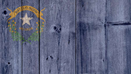 USA Politics News Concept: US State Nevada Flag Wooden Fence