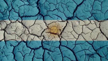 Crisi politica o concetto ambientale: crepe nel fango con la bandiera dell'Argentina