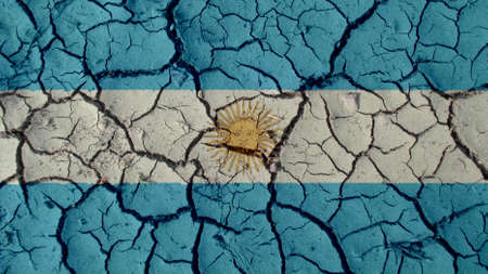 Political Crisis Or Environmental Concept: Mud Cracks With Argentina Flag Stock Photo