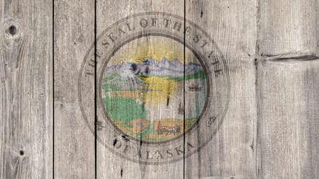 USA Politics News Concept: US State Alaska Seal Wooden Fence Background