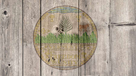 USA Politics News Concept: US State Vermont Seal Wooden Fence Background
