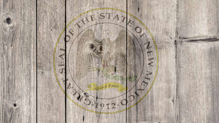 USA Politics News Concept: US State New Mexico Seal Wooden Fence Background