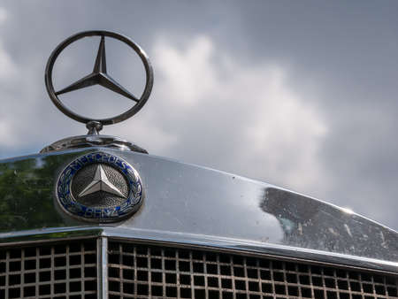 BERLIN, GERMANY - MAY 19, 2019: Classic Mercedes Logo And Star On A Mercedes Vintage Car Against A Cloudy Sky