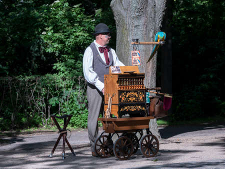 BERLIN, GERMANY - JUNE 8, 2019: A Barrel Organ Player With A Parrot In Berlin, Germany