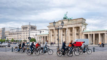 BERLIN, GERMANY - JULY 8, 2019: Cyclists Riding Bicycles At Brandenburg Gate In Berlin, Germany In Summer