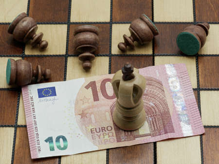 Money Rules Concept: King Chess Piece Standing On A 10 Euro Banknote With Defeated Lying Pawns On A Chess Board Stock fotó