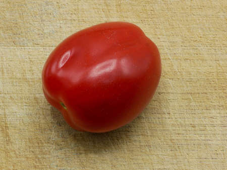 Close-up of A Roma Tomato Also Called Italian or Plum Tomato On A Cutting Board
