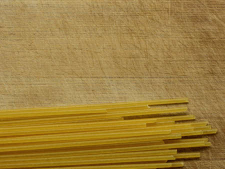 Close-up of Uncooked Spaghetti On A Scratched Wooden Cutting Board, Top View With Copy Space