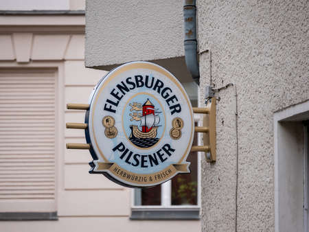 BERLIN, GERMANY - FEBRUARY 12, 2020: Advertisement: Logo of German Flensburger Pilsener Beer Outside At A Wall In Berlin, Germany