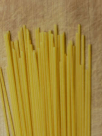Close-up of Uncooked Spaghetti On A Scratched Wooden Cutting Board, Top View, Blurry Background