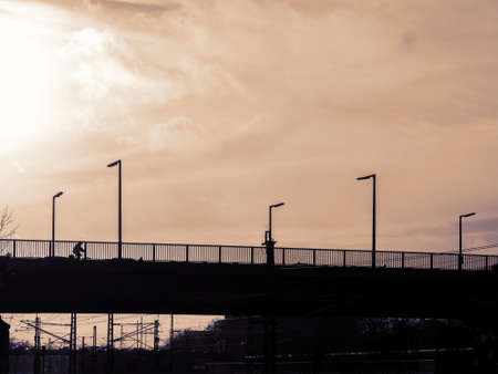 Silhouette of A Bridge With An Unidentifiable Cyclist Against A Sunny Cloudy Sky
