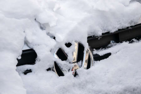 Close-up of A Snow-capped VW Logo On A Car
