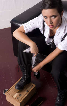 A young woman shines up her old boots Stockfoto