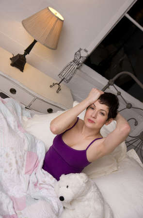 A pretty brunette woman in her pajamas just wakes up photo