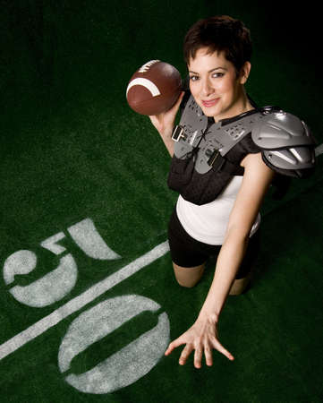 A female football player smiles as she throws a forward pass Stock Photo - 14500916