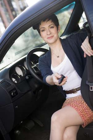 A pretty woman hands you the car keys Imagens