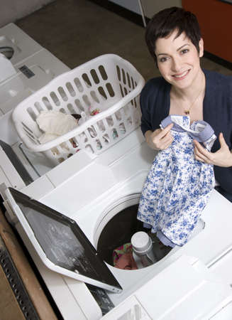 A woman pulls clothes from the washer at the laundromat Banco de Imagens