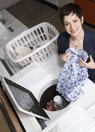 lavadora con ropa: Una mujer saca la ropa de la lavadora en la lavander�a