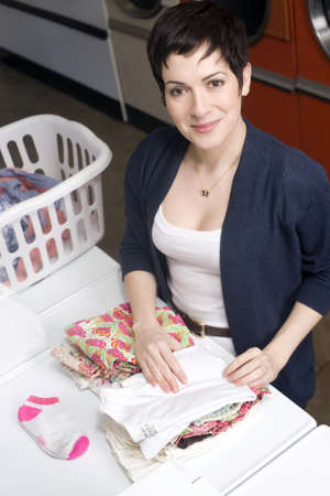 A beautiful thirty something woman folds her laundry photo