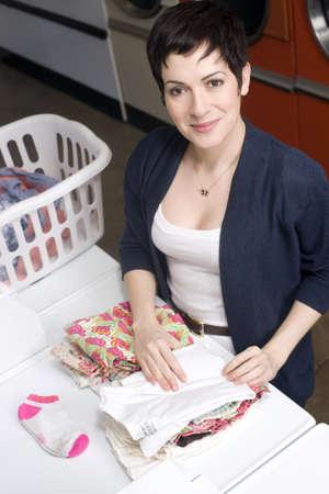 A beautiful thirty something woman folds her laundry Banco de Imagens