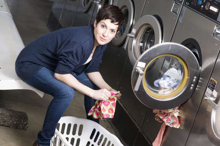 A woman toils at the laundromat Stock Photo