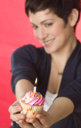 A pretty brunette holds her birthday cupcake Stock Photo - 14499233