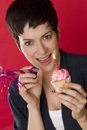 A woman smiles before blowing out her candle and eating her cupcake Stock Photo - 14500917