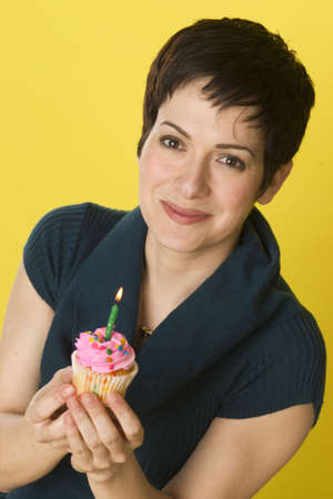A woman smiles before blowing out her candle and eating her cupcake photo