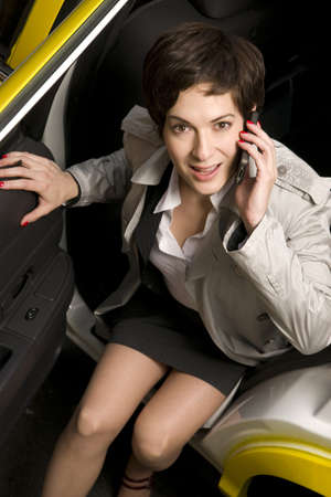 A female taxi cab rider looks right at the camera
