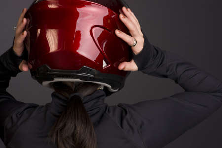 A red full face helmet is put on by a woman rider Stock Photo - 14499184