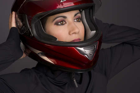 A full face helmet is put on by a woman rider photo