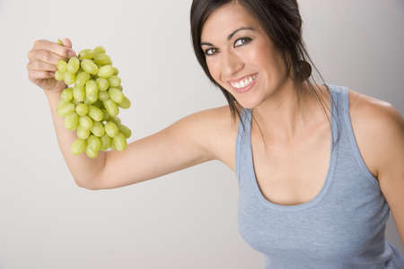 Beautiful Brunette Eats Grape Stock Photo - 14593316