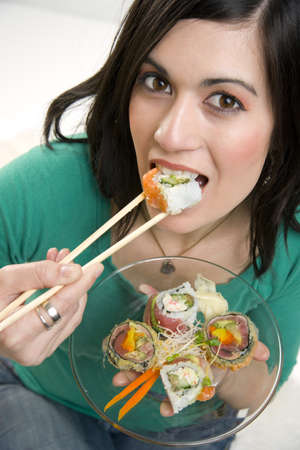 A 29 year old woman takes a bite of a Sushi Roll Stock Photo - 14593318