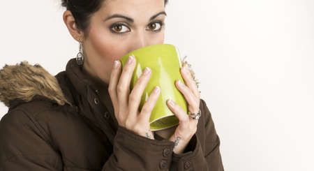 warms: A beautiful woman warms up with a mug of Java