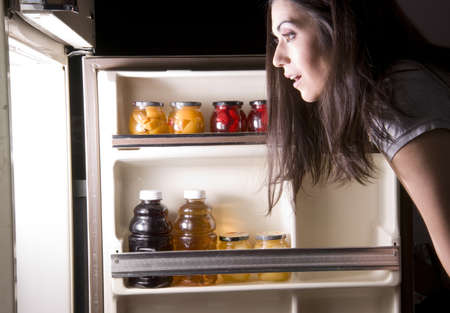 refrigerator with food: A woman raids the refrigerator late at night