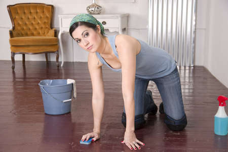 Housekeeper on her knees looking at the Camera Stock Photo