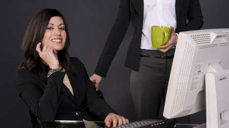 29 year old woman takes has a co-worker visit her desk Stock Photo - 14669503