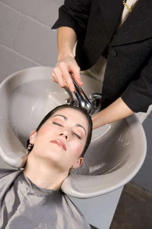 woman washing hair: A day at the salon starts with shampoo