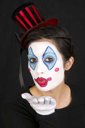 A funny female clown blows you a kiss