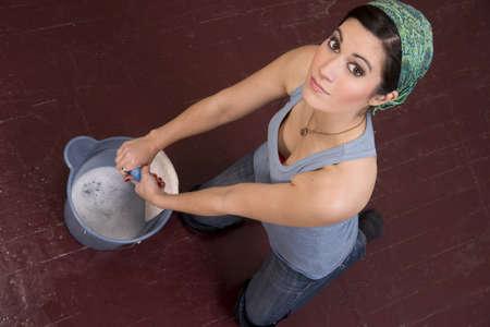 Housekeeper on her knees hand washing the floor