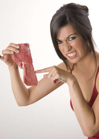 meat diet: Beautiful Brunette holds raw red steak meat Stock Photo