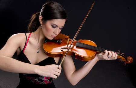 Beautiful Violinist looks at her instrument photo