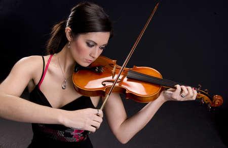 m�sico: Violinista hermoso mira a su instrumento Foto de archivo
